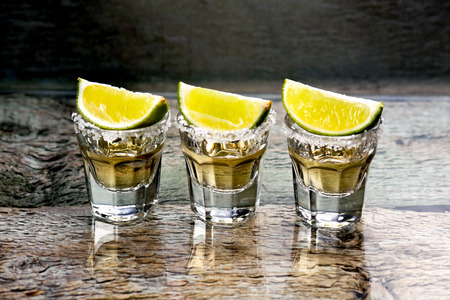 wood backgrounds: Glasses of gold tequila with lime in the  bar Stock Photo