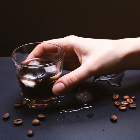 Tasty ice coffee with coffee beans and hand