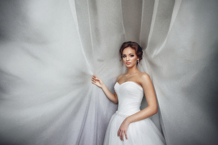 sexy bride: Beautiful sexy bride in white dress posing under curtain Stock Photo