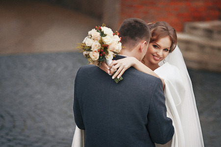 newlywed couple: Happy newlywed couple with bouquet hugging outdoors