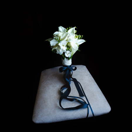 Brides bouquet staying on the gray pillow
