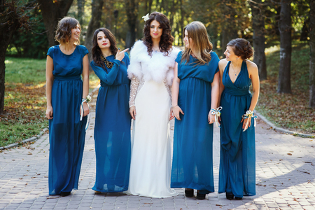 bridesmaid: Bride with bridesmaid playing fool in the park Stock Photo