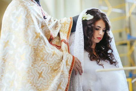 Bride standing with a preacher during the ceremony