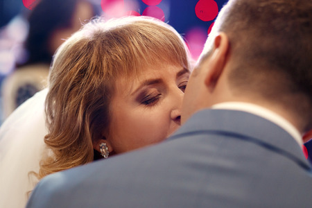 earing: Happy beautiful newlyweds kissing in restaurant