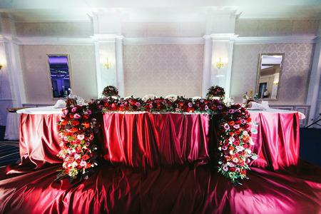tela seda: Newlyweds table with the red silk cloth decorated with roses