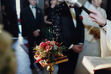 christian marriage: Priest sprinkles wedding rings on the red bouquet Stock Photo