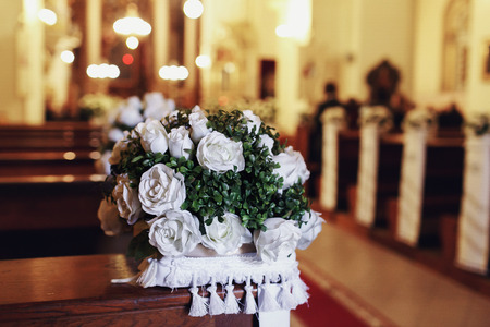 Church bench decorated with white roses and pillows