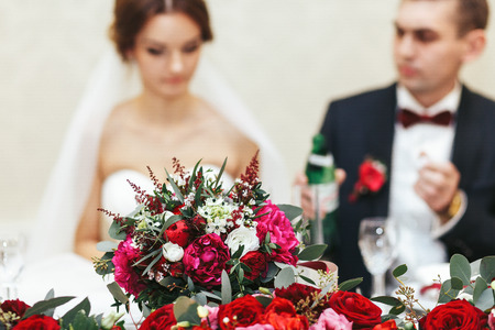 Bouquet of peonies, ranunculus and roses stand in the front of just married
