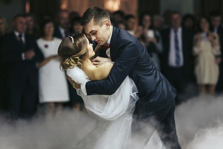 Verlobte hält Braut in seinen Händen beim Tanzen im Rauch Standard-Bild - 64223767