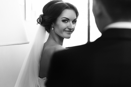 bridegrooms: Bride looks with a smile over bridegrooms shoulder
