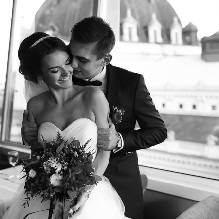 panoramic windows: Fiance holds bride by the shoulders before the panoramic windows Stock Photo