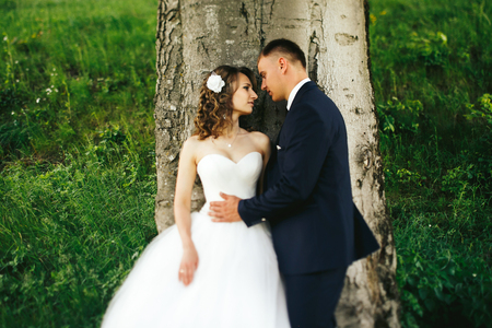 Man holds brides waist tenderly behind a tree Stock Photo