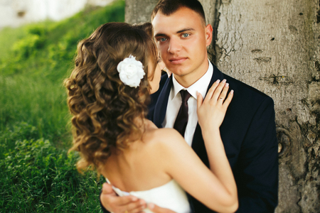 Blue-eyed groom looks thoughtful holding bride in his hugs