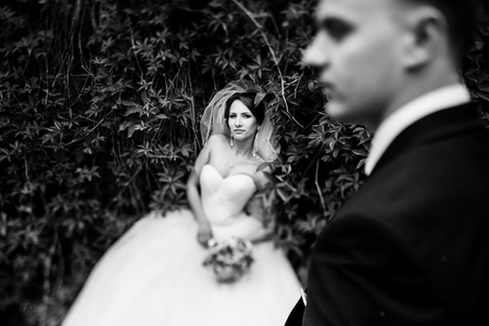 misterious: Bride lies on the green hedge behind a fiance Stock Photo