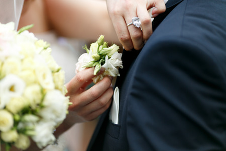 boutonniere: Delicate brides hands pin a boutonniere in grooms jacket Stock Photo