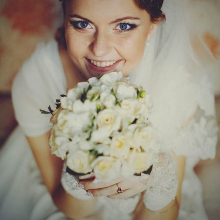 Bride with blue eyes and freckles looks funny while smiles