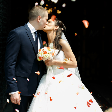 Just married couple kisses in the rain of rose petals Stockfoto