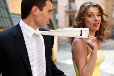 grimaces: Lady in yellow pulls mans tie and grimaces Stock Photo