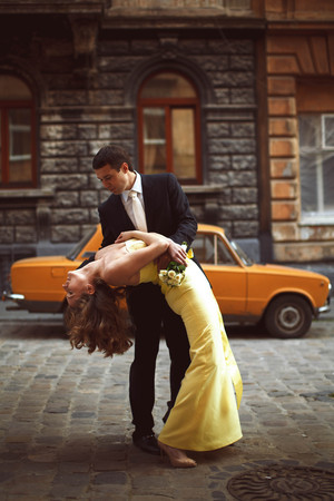 romantic man: Groom leans over a bride in yellow dress