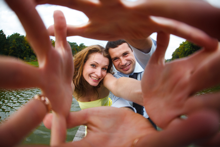 reach out: Man and woman smile reaching their hands out to the camera