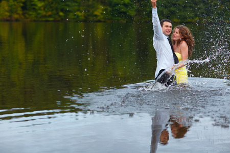 embracement: Man splashes water hugging woman in yellow dress