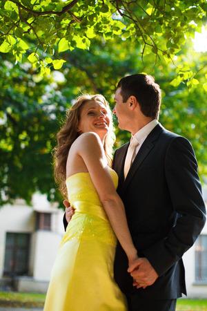 Sun highlights woman in yellow dress while she hugs a man
