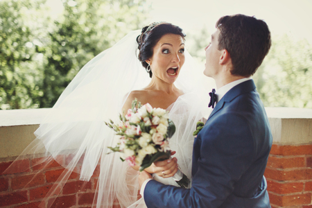 hugged: Funny bride looks shocked being hugged by a groom