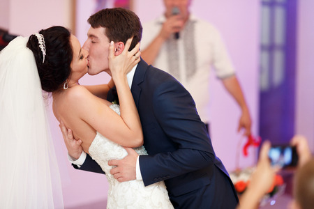 A passionate kiss of just married couple during their first dance