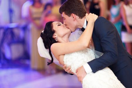 新郎は、彼らの最初のダンスの中に彼女を曲げて花嫁をキスします。