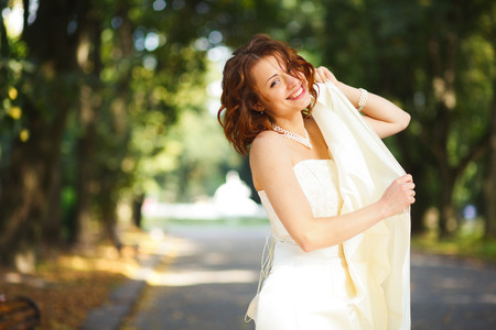 Sincerely - bride holds her dress in hands while posing in park Stock Photo