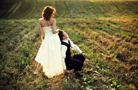 somewhere: Supporting - groom rests on brides legs somewhere on the field Stock Photo