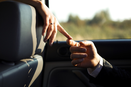 embracement: Just a touch - fingers of newlyweds touch in the lights of the sun  in car Stock Photo