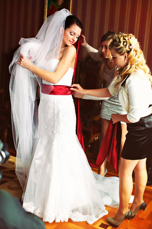 get ready: Bridesmaids help bride to get ready for a ceremony Stock Photo