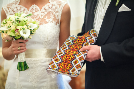 Groom holds a embroidered wedding towel