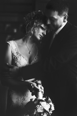 embracement: A black and white picture of a groom hugging a thoughtful bride while she leans her head on his shoulder Stock Photo