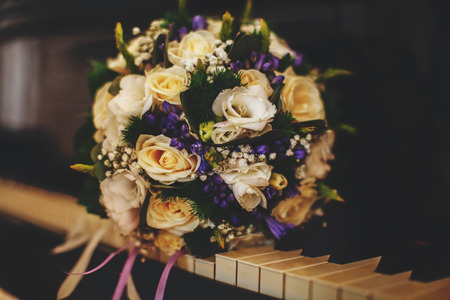 arm bouquet: A wonderful brides bouquet of white roses and violets lies on the piano