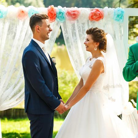 Brides hold hands near wedding archway