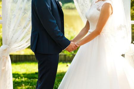 archway: Brides hold hands near wedding archway
