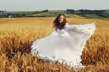 sways: Happy bride sways her dress standing on the field