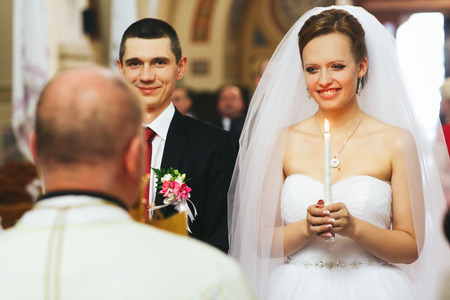 sincerely: Bride and groom smile sincerely standing in the front of the priest during a ceremony