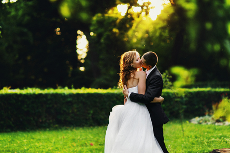 passionate kiss: A passionate kiss of newlyweds somewhwere in the park on the sunset Stock Photo