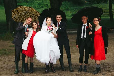 gumboots: Newyweds, bridesmaids and groomsmen pose under umbrella in gumboots