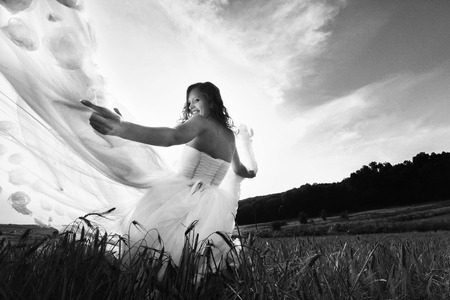 A black and white picture of a bride while sun shines through her blown away dress