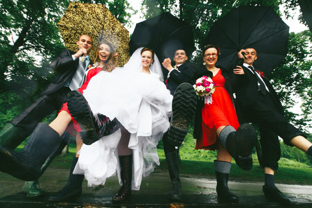 gumboots: Newlyweds and their friends hold legs in the gumboots up Stock Photo