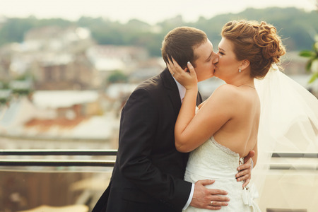 Groom kisses bride after a wedding ceremony