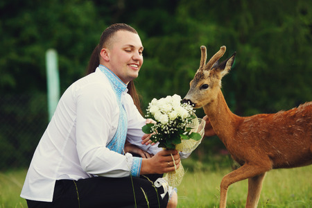Little funny deer tries to eat a wedding bouquet from grooms hand