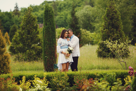 Groom holds brides shoulder tenderly standing between bushes in the park