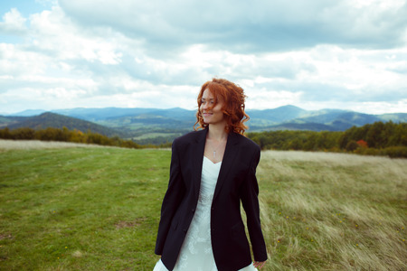 Bride smiles standing on the field in grooms jacket with great mountain landscape hidden behind her