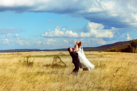 Groom rises bride up standing on the field under a deep blue sky