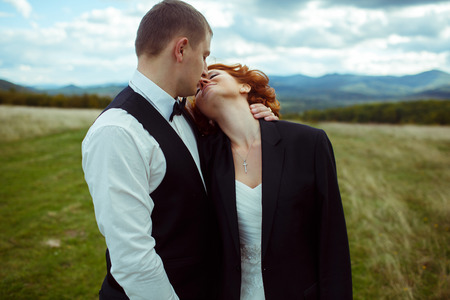 reaches: Bride reaches grooms face for a kiss standing on the field in windy weather Stock Photo